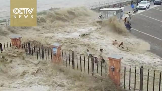 Welle spült Touristen weg
